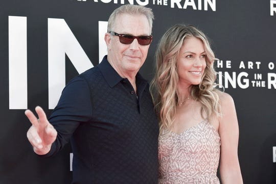 "Kevin Costner, left, and wife Christine Baumgartner attend the LA premiere of ""The Art of Racing in the Rain"" in this, Aug. 1, 2019, file photo in Los Angeles."