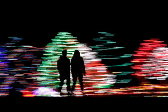 People are silhouetted against a Christmas display, at a park in Lenexa, Kansas.