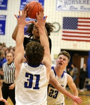 Jionel Howard of Elmira goes up for a shot as Horseheads' Henry Juan (31) and Ryan Scott (23) defend during the Blue Raiders' 54-48 win in boys basketball Dec. 19, 2019 at Horseheads Middle School.