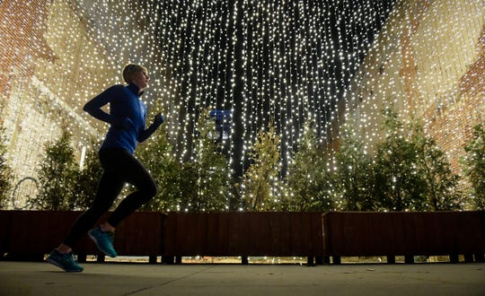 A jogger runs by a curtain of lights as Christmas decorations, provided by Evansville's Economic Improvement District, gives a festive touch to Main Street Thursday evening. The EID, provides help with trash removal, ice and snow removal and special events wraps up its first calendar year in business, December 19, 2019.