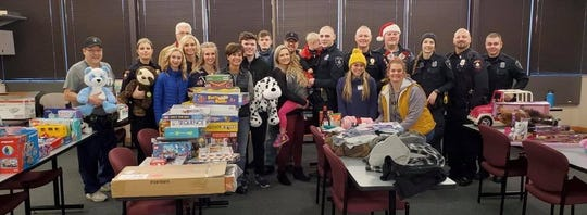 "Members of the Fond du Lac Police Department and volunteers gathered the morning of Friday, Dec. 20 to put organize and distribute gifts and food to 75 local families through the department's ""Adopt-a-Family"" program."