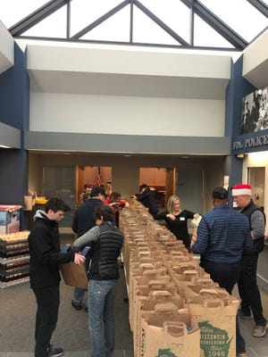 """Volunteers fill Festival Foods grocery bags with items for a Christmas meal as part of the """"Adopt-a-Family"""" at the the Fond du Lac Police Department, Monday, Dec. 20, 2019."""