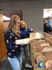 "Peyton Walters, left, and Riley Walters, fill bags for families to receive Christmas meals as part of the Fond du Lac Police Department's ""Adopt-a-Family"" program."