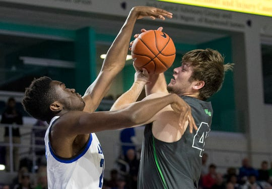 Cayden Baker of Fort Myers tries to take a shot over Mark Williams of IMG Academy in the 2019 City of Palms Classic on Thursday, Dec. 19, 2019, at Suncoast Credit Union Arena in Fort Myers.