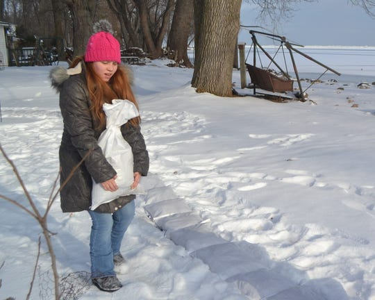 Megan McNabb delivers a sandbag for placement behind Tina Driscoll's home along Green Bay on Thursday.