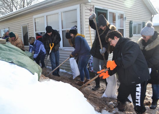 Oconto High School students work to shovel and fill sandbags at the home of Tina Driscoll on County N south of Oconto. At far left is their teacher, Lara Nichols-Timm, and two friends of Driscoll's from Pound, Paul Smith and Deb LeFebre.