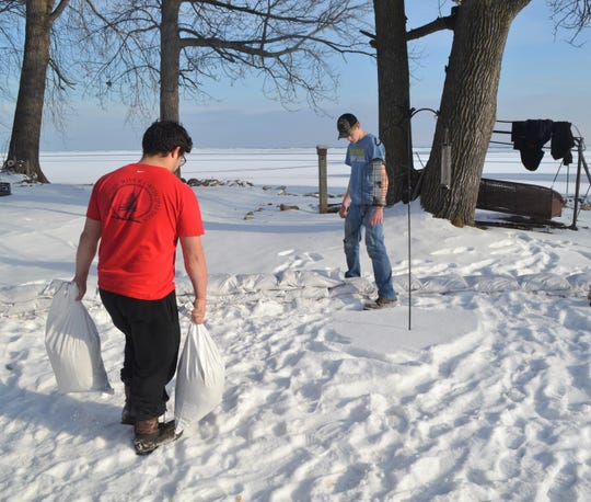 Isaac Diaz carries sandbags to Sterling Heyrman, who arrange the sandbags on the barrier at the bay shore home of Tina Driscoll on Thursday.