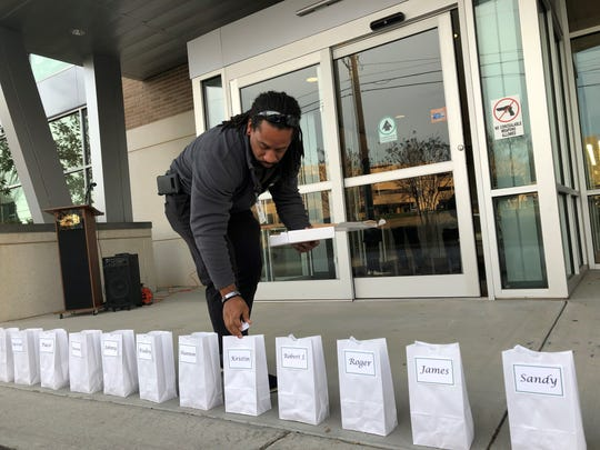 Brandon Cook, New Horizon Homeless Health Care program manager, prepares luminaries in honor of the facility's 18 patients who died in 2019 while experiencing homelessness