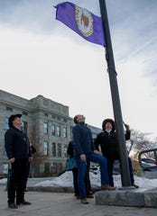 Clarence Sivertsen, left, Gov. Steve Bullock, center and Don Davis watch as the Little Shell tribal flag is raised outside the state Capitol Dec. 20, celebrating the tribe's long-awaited federal recognition.