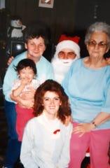 Cheryl Larsen, center, celebrates Christmas with, from left, her mother Rose McMillen holding daughter Megan LeDea, Scott White as Santa Claus and grandmother Ella Harvey.