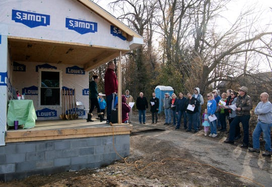 Habitat for Humanity of Henderson's Britney Smith, executive director, far left, welcomes attendees to the Morgan Family groundbreaking at 218 S. Adams Street Friday afternoon. Christina Morgan and her son, Hemi, 16, will be moving into the home when it is completed.