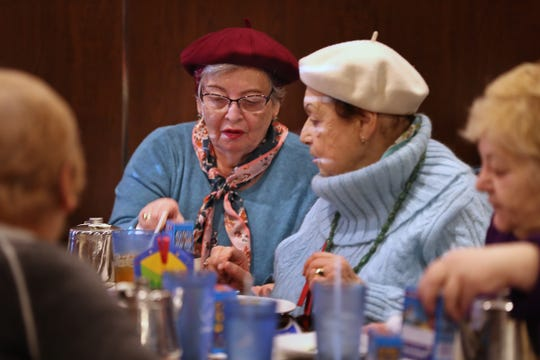 Leah Adelfinskaya (left) and Era Solyar look at Hanukkah decorations as the Kavod group has lunch at The Journey buffet in Indianapolis on Dec. 19.