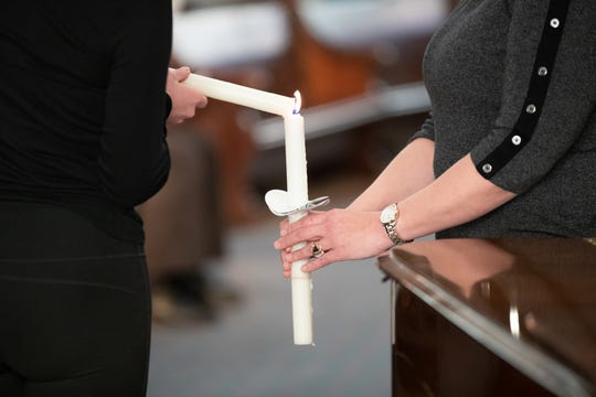 The 2019 Diamond Service Award recipient, Brandi Moran, right, performs her duty as candle lighter for the reading of names, during the annual Coalition for Homelessness Intervention and Prevention memorial service remembering those who have passed away over the last year in Indianapolis, at Roberts Park United Methodist Church, Friday, Dec. 20, 2019.