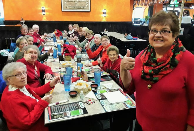 """Photo of women seated at long table. With many sporting colorful Christmas sweaters, the """"Knee Knockers"""" support group gathered earlier this month for lunch. At right is Sherry Carpenter, who founded the group 15 years ago for women who have experienced knee surgery."""