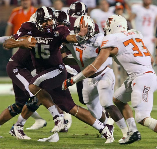 FILE - In this Oct. 12, 2013 file photo, Mississippi State quarterback Dak Prescott (15) tries to get past Bowling Green linebacker Paul Swan (33) in the second half of an NCAA college football game in Starkville, Miss. Prescott's name is already solidified in Mississippi State lore after he came off the bench in the fourth quarter to lead the Bulldogs past rival Mississippi in the Egg Bowl.