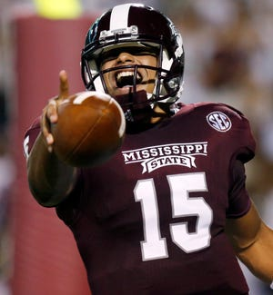 FILE - In this Sept. 21, 2013 file photo, Mississippi State quarterback Dak Prescott (15) celebrates his second quarter touchdown run against Troy in an NCAA college football game at Davis Wade Stadium in Starkville, Miss.Prescott's name is already solidified in Mississippi State lore after he came off the bench in the fourth quarter to lead the Bulldogs past rival Mississippi in the Egg Bowl. Now the sophomore takes over as the team's unquestioned No. 1 quarterback heading into the Liberty Bowl against Rice.