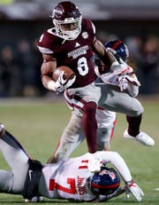 Mississippi State running back Kylin Hill (8) leaps over Mississippi defensive back Jalen Julius (7) on a 30-yard touchdown run during the second half of am NCAA college football game in Starkville, Miss., Thursday, Nov. 23, 2017.