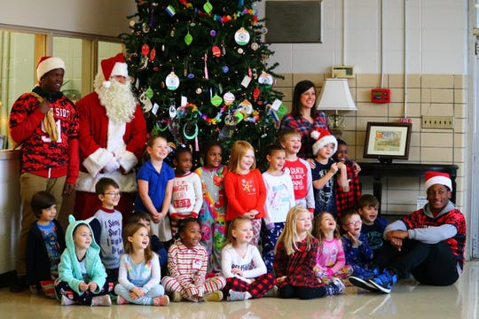 Santa Claus, Timothy Douglas and Devion Woods take a picture with a class at Community Montessori.
