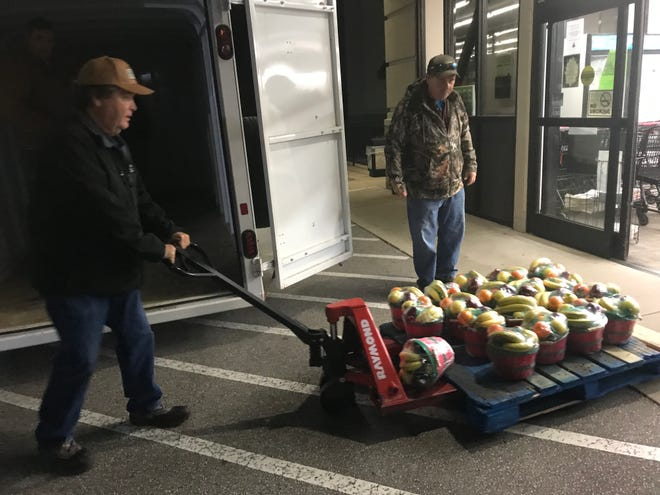 Members of a men's prayer group from Antioch Baptist near Three Way load fruit baskets into a trailer before taking them to the Madison County Sheriff's Department on Friday.