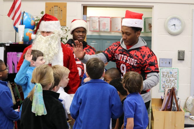 Timothy Douglas talks with children at Community Montessori as he accompanies Santa Claus on a visit to the school.