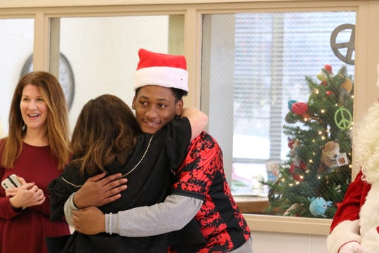 Timothy Douglas, a football player at South Side, gets a hug from a teacher during a visit to Community Montessori with Santa Claus this week.