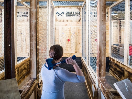 News Sentinel reporter Maggie Jones tries her hand at ax throwing at Craft Axe Throwing's new location at 119 W. Fifth Ave., Suite 150, in Knoxville on Friday, Dec. 20, 2019. Craft Axe Throwing will open to the public on Dec. 31, 2019.