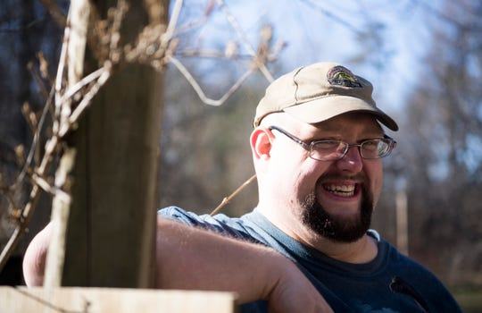 Chris Kastner smiles in his homemade dinosaur park Backyard Terrors, which is located in his own back yard, Thursday, Dec. 19, 2019. Sullivan County has issued multiple code violations, the cost of which threatens to shut the park down.