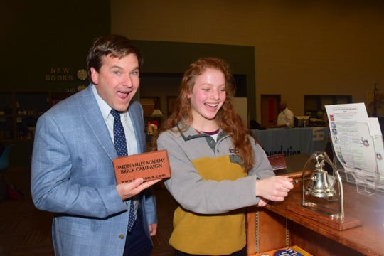 """Principal Rob Speas seems particularly impressed with Annabel Miller, 14, who just sold a brick at a phonathon sponsored by the Hardin Valley Academy Foundation held at the school Thursday, Dec. 12. """"It was really easy,"""" said Miller. """"I had a script and the sale made itself."""""""