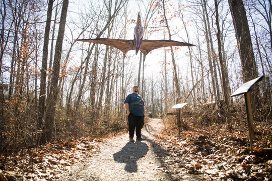 Chris Kastner poses with one of his dinosaur sculptures in his homemade dinosaur park Backyard Terrors, which is located in his own back yard, Thursday, Dec. 19, 2019. Sullivan County has issued multiple code violations, the cost of which threatens to shut the park down.