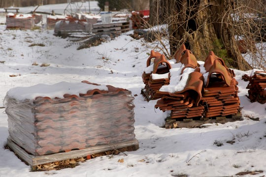 Red roof tiles sit on pallets near the historic Grand View Cemetery caretaker's cottage, Friday, Dec. 20, 2019 in West Lafayette.
