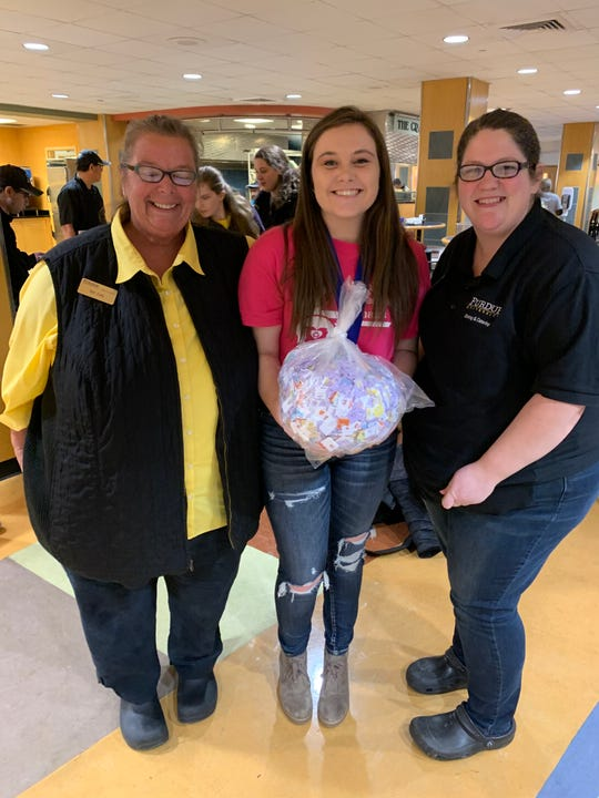 Danielle Rothchild, center, poses with a bag full of donated bread tags with two Purdue employees.