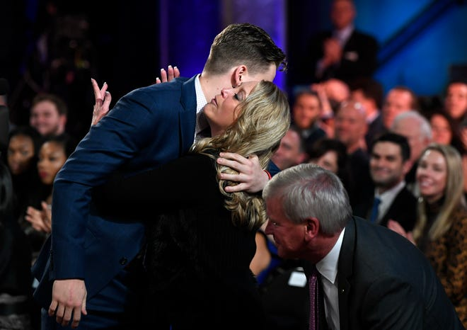 NCAA college football player, LSU quarterback Joe Burrow, left, hugs his mother, Robin, after he is announced as the Heisman Trophy winner, Saturday, Dec. 14, 2019, in New York. Burrow's father, Jim, is at right. (Todd Van Emst/Pool Photo via AP)