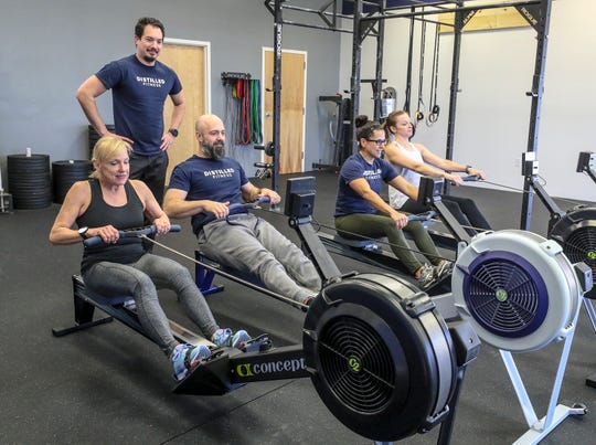 Jason Kelly keeps tabs on Kirby Adams, Chris Smith, Vanessa Smith and Callie Kelly on the rowing machines at Distilled Fitness in Lyndon.