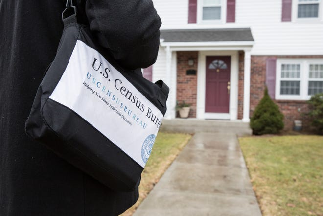 A U.S. Census worker practices visiting a Providence, Rhode Island home during a simulation in 2018.