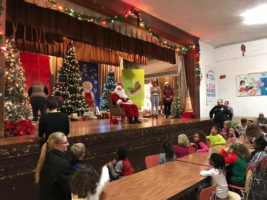 Youngsters at Friendly House Thursday night were glad when Santa took his seat on the stage. It meant it was time for talking to Santa and getting a present  during the annual party sponsored by Mansfield Kiwanis Club.