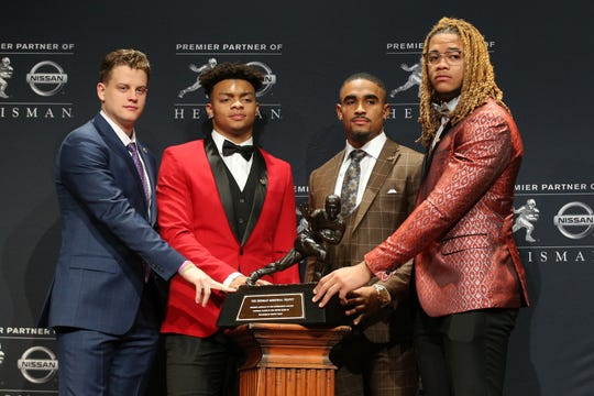 LSU quarterback and Ohio State grad Joe Burrow (left) and OSU quarterback Justin Fields (second from left) pose with the Heisman Trophy, along with fellow Oklahoma quarterback Jalen Hurts and OSU defensive end Chase Young prior to the ceremony. Burrow was named the winner in a landslide victory.