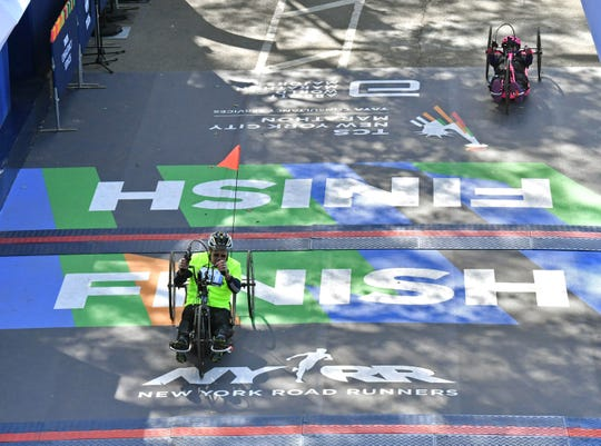 The Rev. Dale Grubba crosses the finish line in the New York City Marathon in November, placing 40th among hand-cyclists eight months after suffering a heart attack and barely three months after undergoing back surgery.