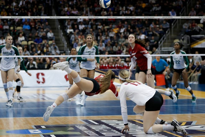 Wisconsin's Lauren Barnes, center, dives for a dig Thursday night in Wisconsin's semifinal victory over Baylor Thursday night.