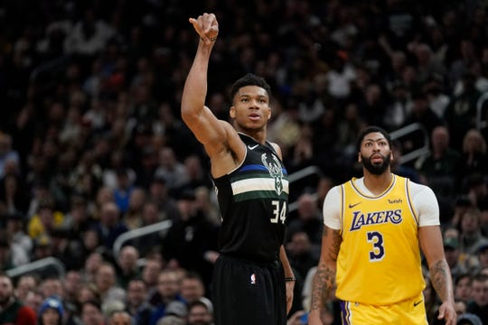 Giannis Antetokounmpo of the Bucks makes one of his 5 three-pointers on the night in front of Lakers center Anthony Davis.