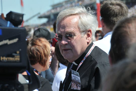 The Rev. Dale Grubba stands on the grid at the Indianapolis Motor Speedway, waiting to pray with driver Kurt Busch before the 2014 Indianapolis 500.