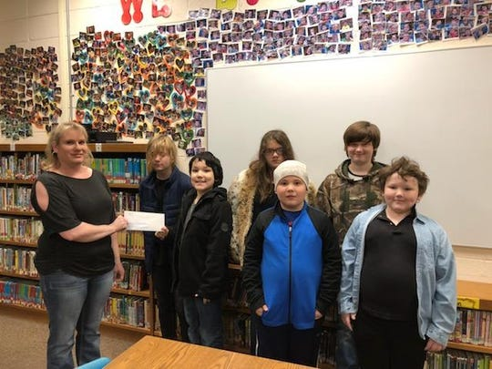Alternative Learning Environment students at Cotter's Amanda Gist Elementary spent the last two weeks making and selling holiday ornaments to staff members to raise money for Serenity House. The students had hoped to raise $50 but ended up collecting $184. Shown presenting a check to Serenity House representative Leslie Rouse is (left to right) Aiden Wilkenson, Nate Salinas, Carleigh Vines, Beau Weaver, Chevy Findley, Scottie Vanscoy. Not pictured is Julian Rowand and Chris Rouse. Shown working on their ornaments in the classroom are (left to right) Carleigh Vines, Scottie Vanscoy, Nate Salinas, Chevy Findley and Beau Weaver.
