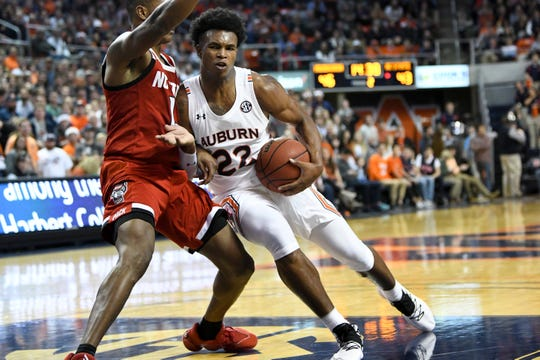 Auburn guard Allen Flanigan (22) drives past North Carolina State guard Dereon Seabron (1) during the second half of an NCAA college basketball game Thursday, Dec. 19, 2019, in Auburn, Ala. (AP Photo/Julie Bennett)