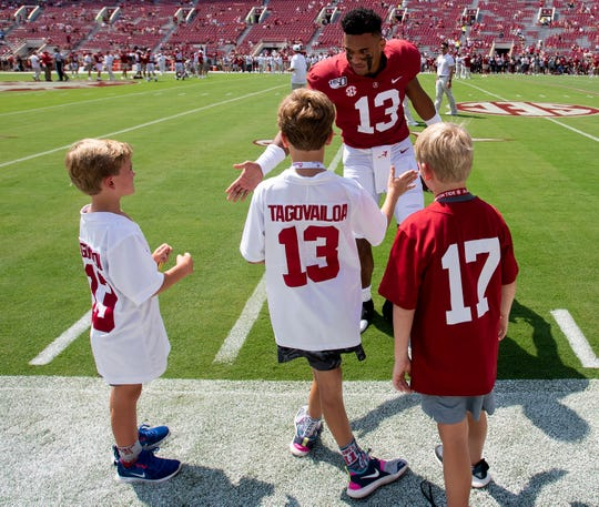 Alabama quarterback Tua Tagovailoa (13) greets young fans on the sidelines as the team warms up before the New Mexico State game at Bryant-Denny Stadium in Tuscaloosa, Ala., on Saturday September 7, 2019.