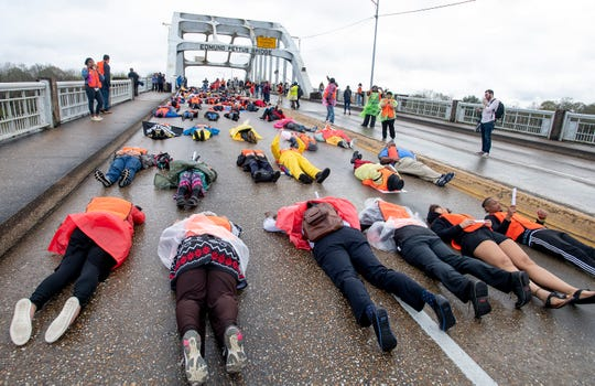 Reenactors lay down on the Edmund Pettus Bridge during the Bloody Sunday March reenactment in Selma, Ala., on Sunday March 3, 2019. Sunday is the 54th commemoration of the 1965 Bloody Sunday bridge crossing.