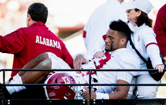 Alabama quarterback Tua Tagovailoa is carted from the field under the care of Alabama's director of behavioral medicine, Ginger Gilmore-Childress (right), after being injured against Mississippi State in Starkville, Ms. on Nov. 16, 2019. The injury was a season ending hip dislocation.
