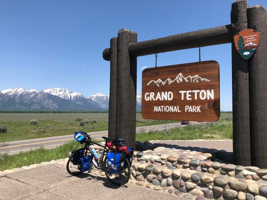Freed's bike in front of a sign at Grand Teton National Park