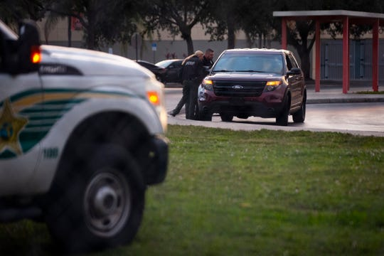 Collier County Sheriff's Office deputies talk to a driver during drop-off in the morning at Lely High School in East Naples on Friday, December 20, 2019. An adult education student was shot and killed on the school grounds on Thursday night.