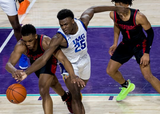 Jarace Walker of IMG Academy and Malcolm Chimezie of Archbishop Stepinac reach for a loose ball in the 2019 City of Palms Classic on Friday, Dec. 20, 2019, at Suncoast Credit Union Arena in Fort Myers.