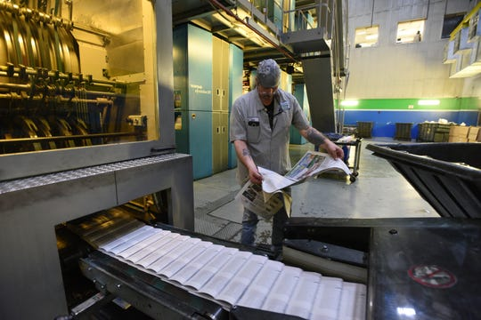 Lee Van Wagenen,press room manager,checks the quality of the printingNewspaper production process at the Rockaway facility