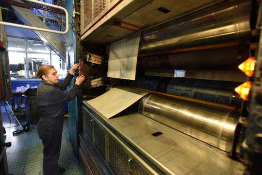 Mariam Madrid attaches plates to the pressNewspaper production process at the Rockaway facility